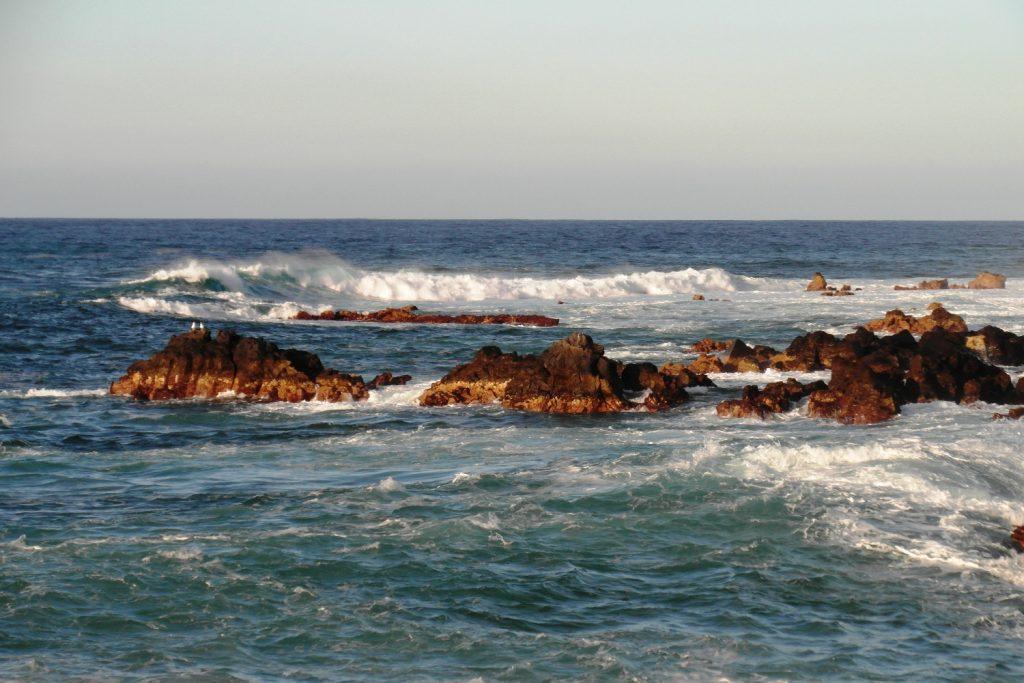 Волны разбиваются о камни очень красиво