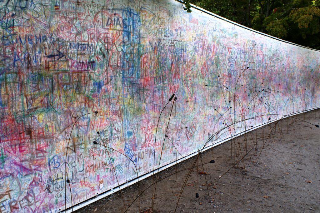 Необычная стена, рядом из земли торчат карандаши на проволоке, можно подойти и написать что угодно