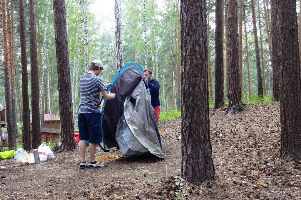 Парни собирают палатку, очень необычная конструкция