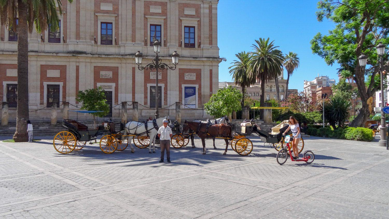 """Лошадки на фоне """"Архива Индий"""" - здания, напоминающего о временах, когда Испания была империей, имеющей немало колоний, называемых когда-то Индиями"""