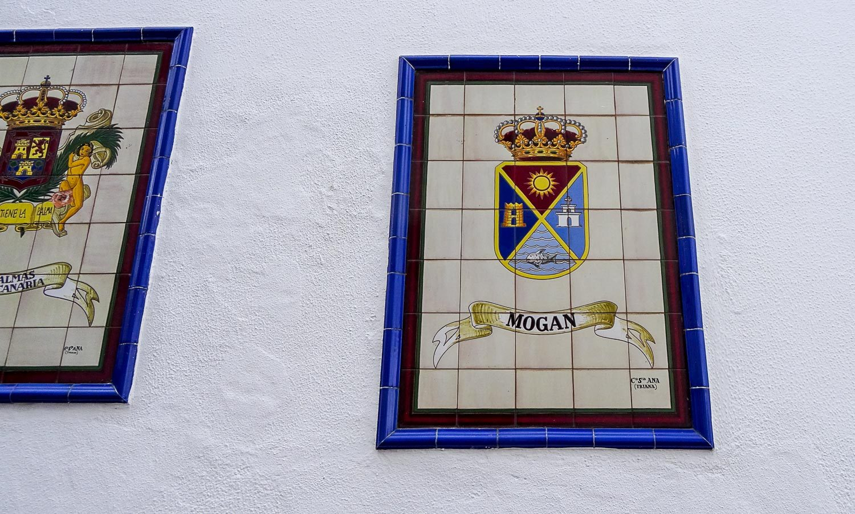 Над лавочками - гербы разных городов