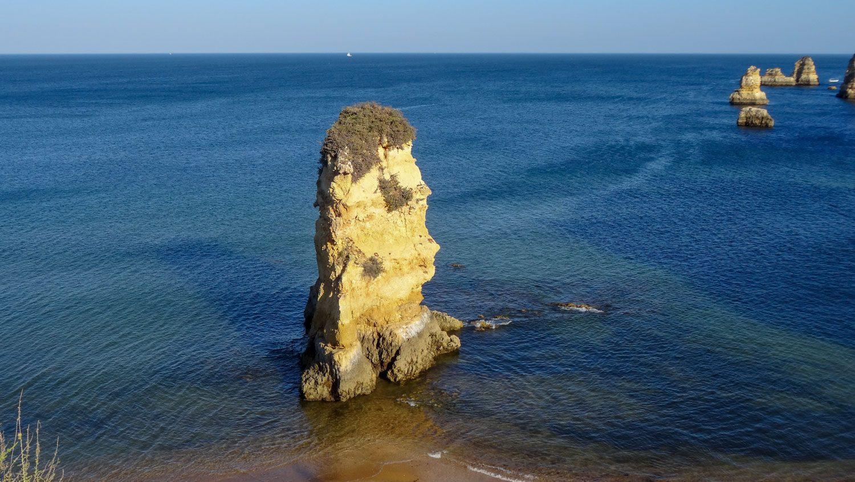 Из воды торчит камень, поросший зеленью