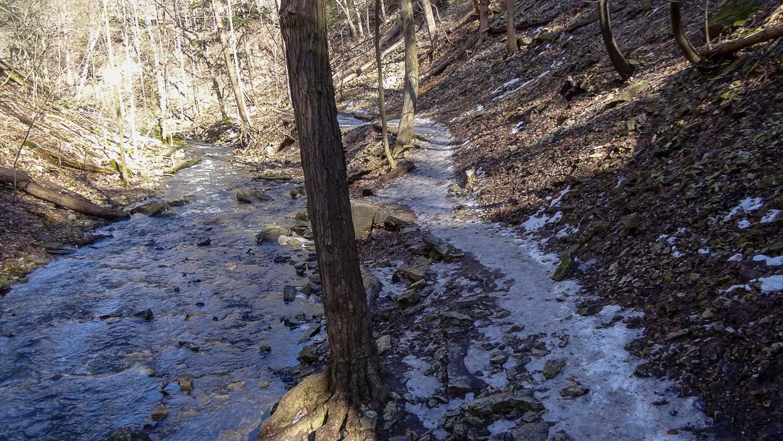 Справа холм, слева речка, на тропинке лед