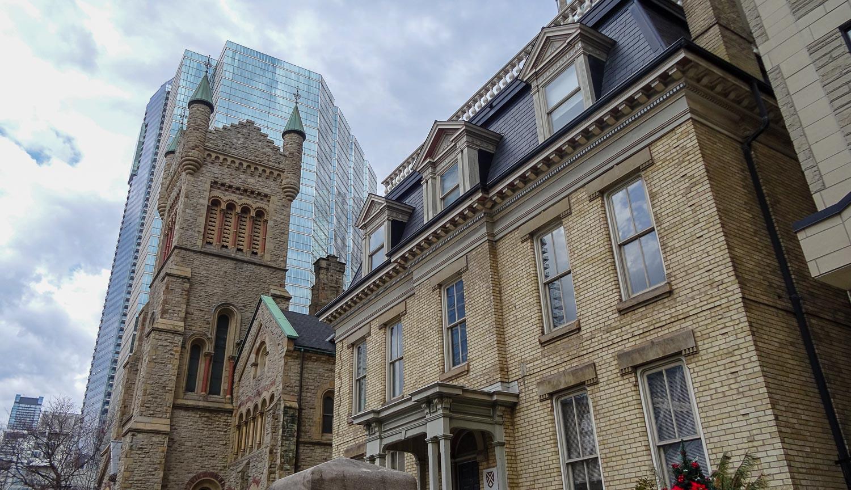 Кирпичные здания на фоне современных небоскребов из стекла и бетона