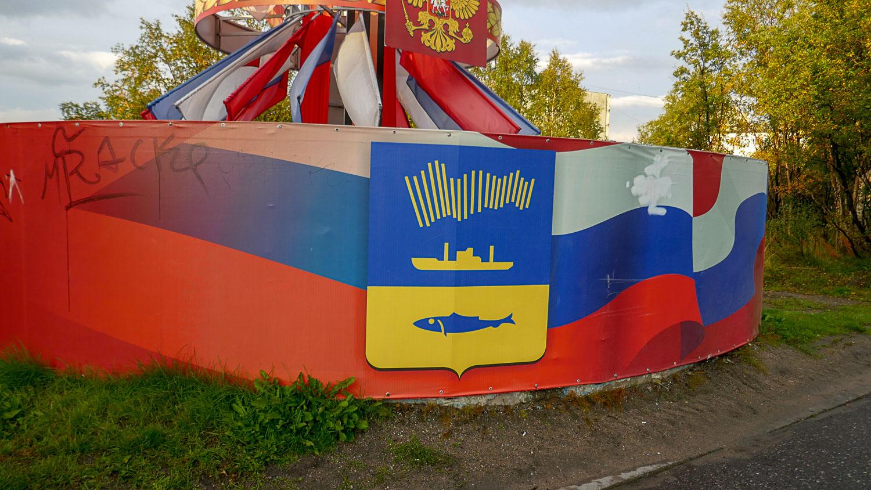Герб: полярное сияние, корабль и рыба